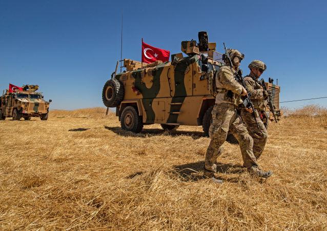 Les troupes américaines marchent près d'un véhicule militaire turc lors d'une patrouille conjointe dans un village syrien