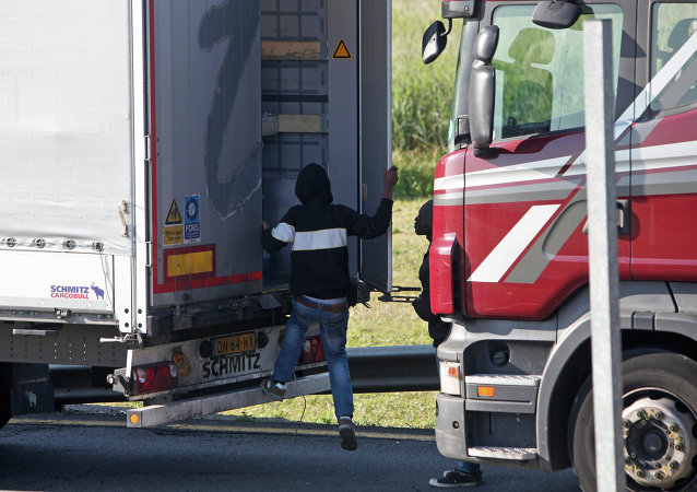 Un migrant monte à bord d'un camion à Calais pour tenter de traverser la Manche, le 24 juin 2015 (image d'illustration)