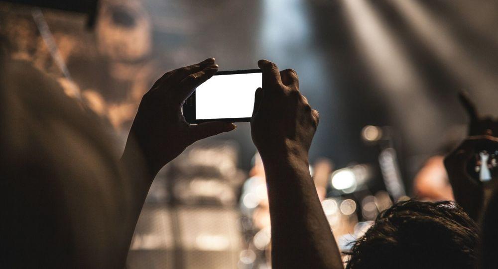 Spectateur avec son smartphone en concert