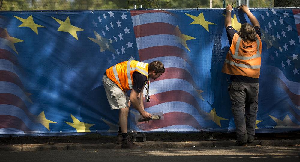 Des ouvriers accrochent des rideaux avec des motifs de drapeau américain et européen