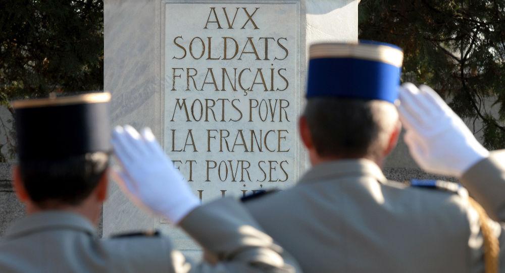 Des soldats français font un salut devant un monument lors d'une commémoration de la fin de la Grande Guerre.
