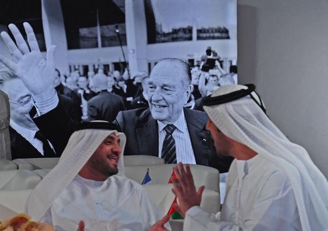 Des invités devant un grand portrait de Jacques Chirac pendant une cérémonie à l'occasion du deuxième anniversaire du Louvre Abou Dhabi.