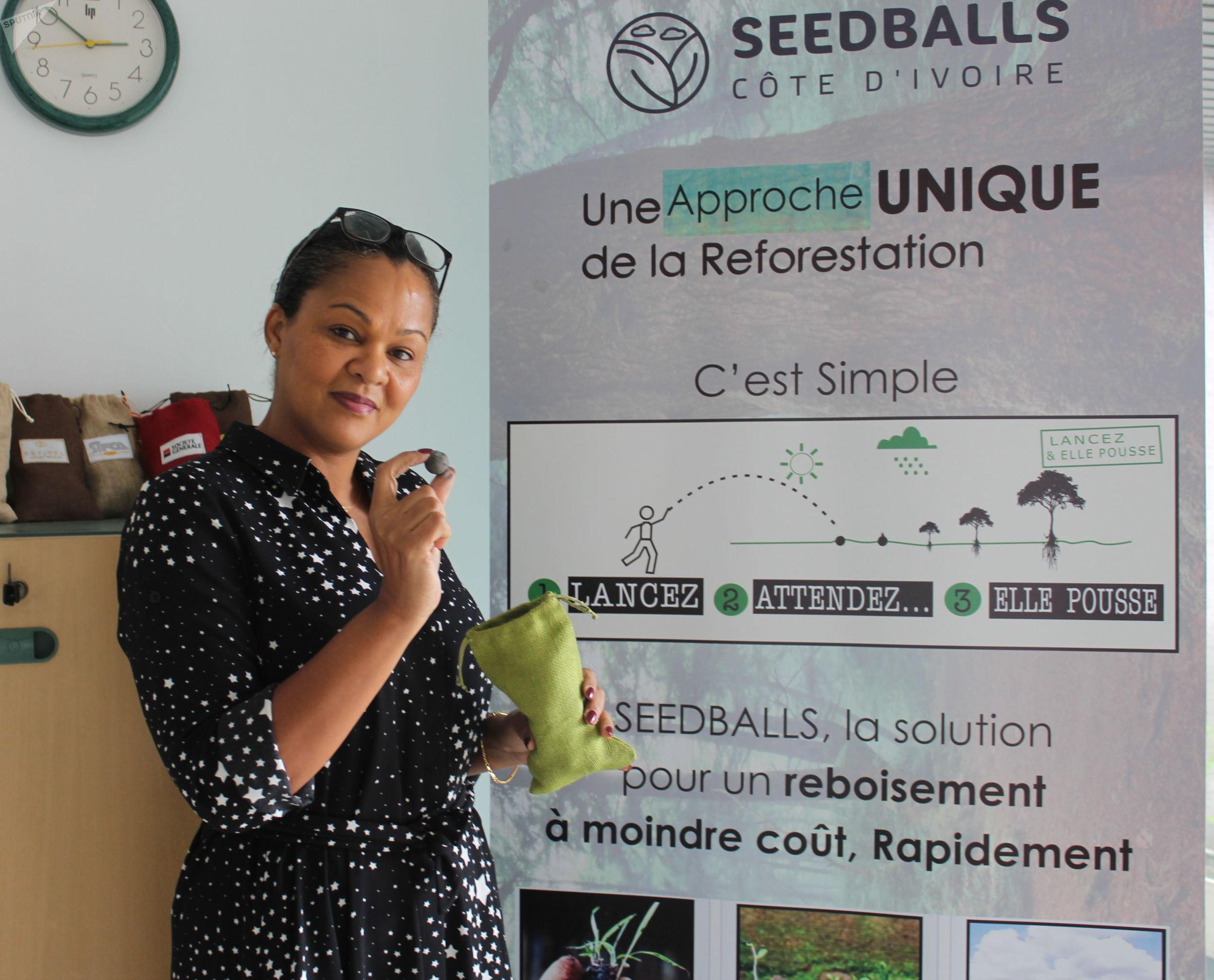 Sarah Traboulsi avec une seedball devant son panneau de campagne de reforestation