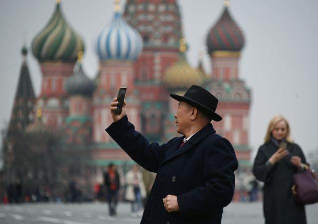 Un touriste se fait photographier sur la Place Rouge