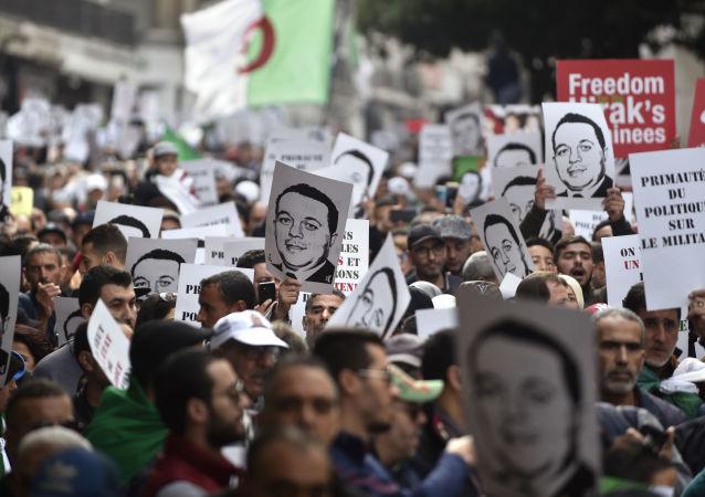 Les Algériens défilent en brandissant des pancartes à l'effigie d'Abana Ramdane à Alger, le 27 décembre 2019.