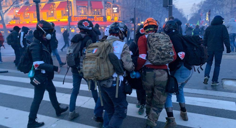 Des street medics évacuent un blessé hors de l'acte 62 des Gilets jaunes, le 18 janvier 2020