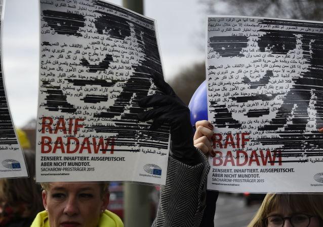 Des membres de l'ONG Amnesty International brandissent des portraits de Raif Badawi devant l'ambassade d'Arabie saoudite à Berlin, le 8 janvier 2016.