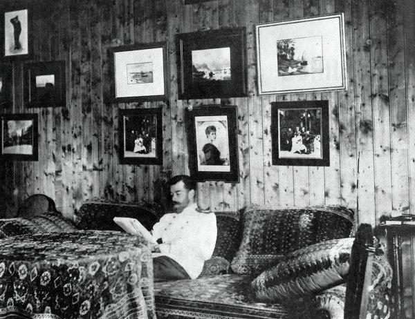 Император Николай II сидит на диване в своей комнате в охотничьем домике