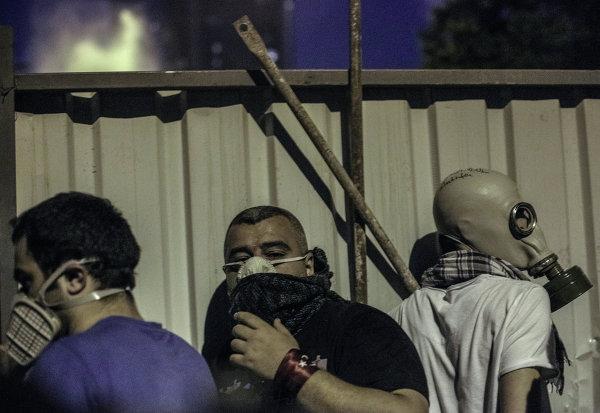 Столкновения протестующих и поПротестующие прячутся от полиции за забором во время столкновения в Стамбуле