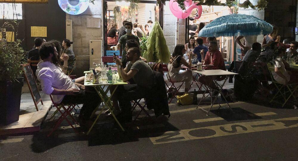 Une terrasse parisienne provisoire sur les places de parking devant un restaurant
