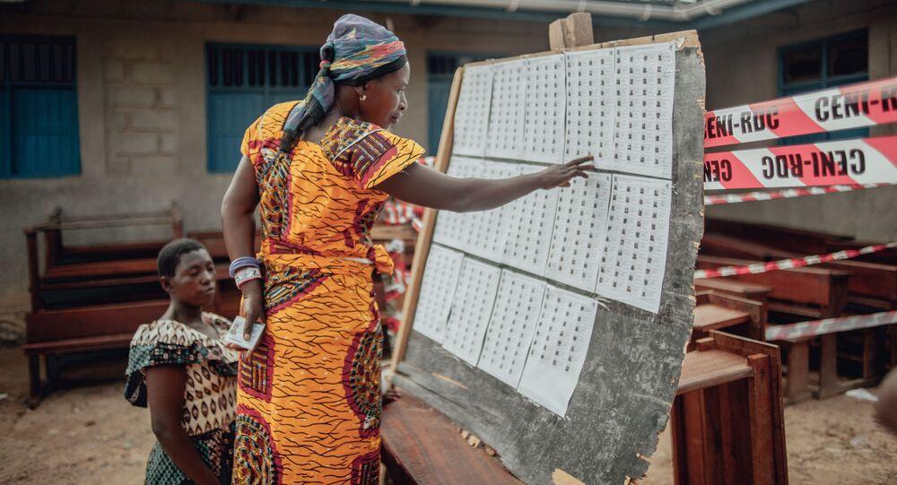 Une femme cherche son nom sur les listes électorales de la CENI en RDC.