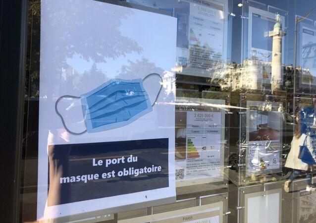 Une affichette Le Port du masque obligatoire dans un café à Paris
