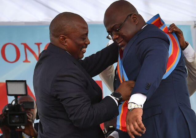 Le Président sortant de la RDC Joseh Kabila aide le nouveau Président à ceindre l'écharpe.