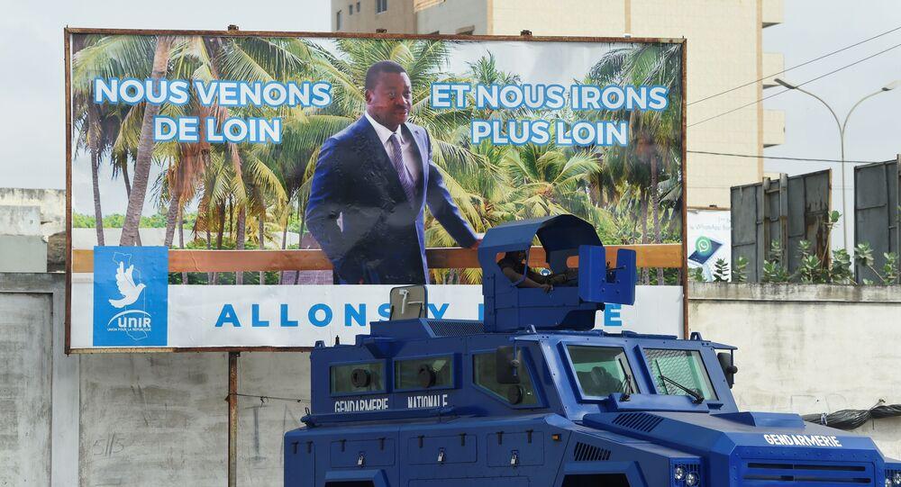 Un véhicule de l'armée togolaise garé devant une affiche électorale du Président Faure Gnassingbé