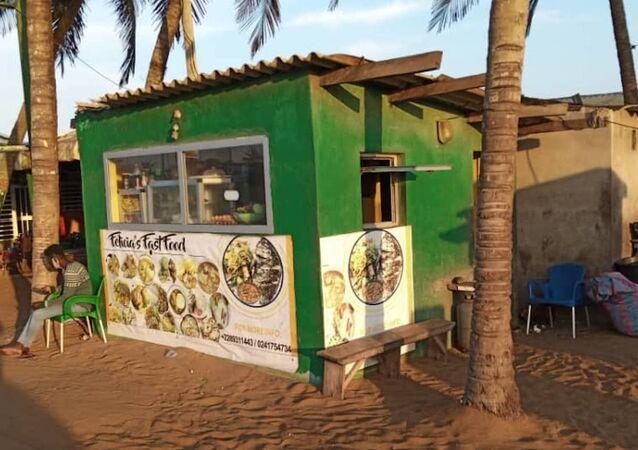 Snack installé sur la plage de Lomé avec derrière, des habitations de fortune