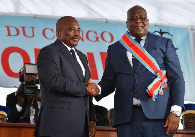 Le président sortant de la République démocratique du Congo Joseph Kabila (à gauche) serre la main du nouveau président Félix Tshisekedi le 24 janvier 2019, après sa prestation de serment à Kinshasa.