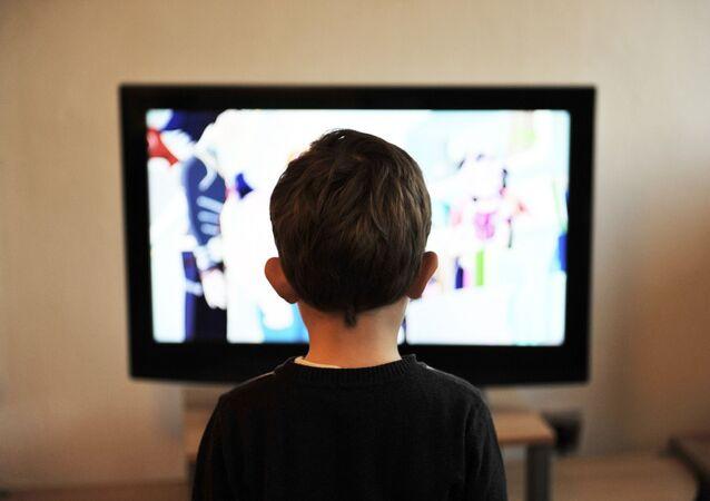 Un garçon devant la télé, image d'illustration