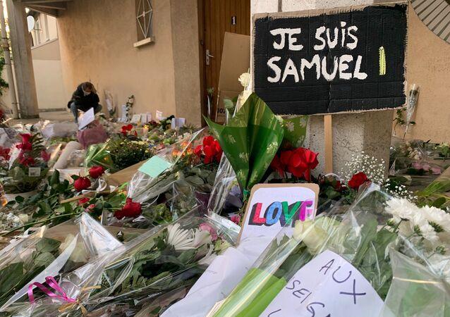 Des enseignants déposent des fleurs devant le collège du Bois d'Aulne à Conflans-Sainte-Honorine en hommage à Samuel Paty, décapité le 16 octobre