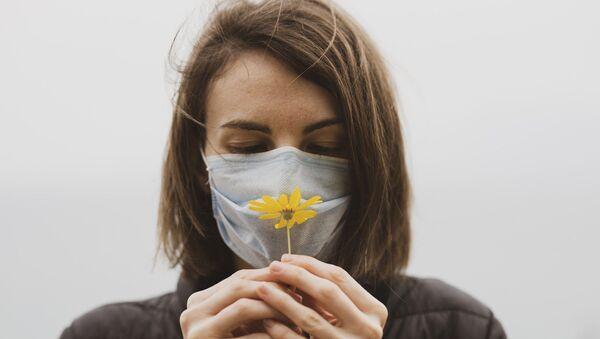Une femme en masque avec une fleur - Sputnik France