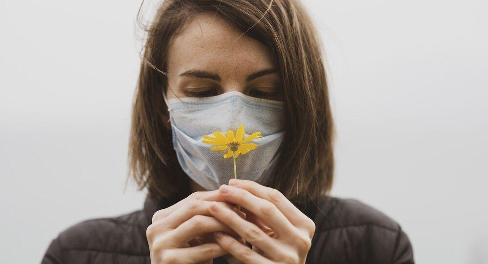 Une femme en masque avec une fleur