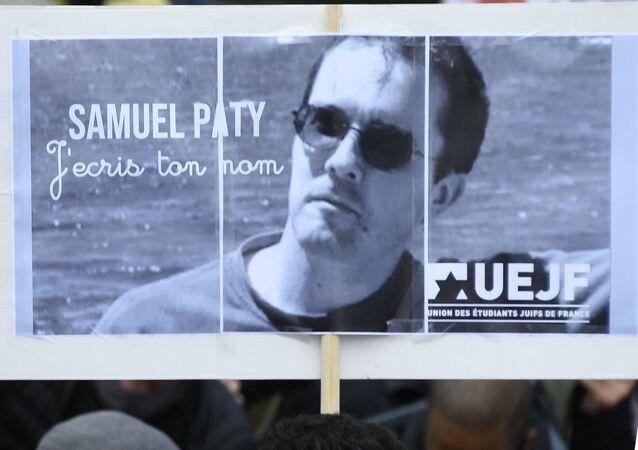Une personne tient une pancarte avec le portrait du professeur Samuel Paty