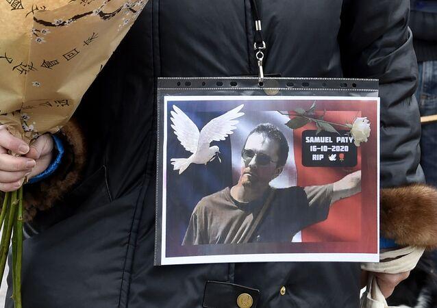 Une femme tient une photo de Samuel Paty
