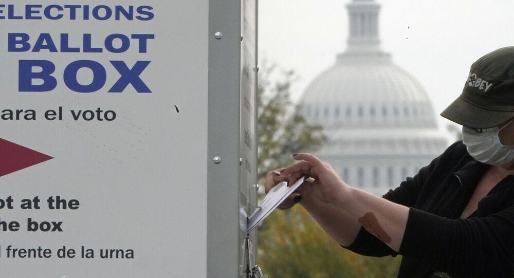 Le dôme du Capitole à l'horizon, un électeur dépose son bulletin dans une boîte de dépôt de votes anticipés, le 28 octobre, Washington