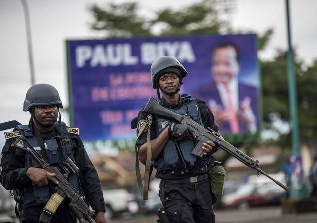 Des militaires camerounais devant une affiche de Paul Biya