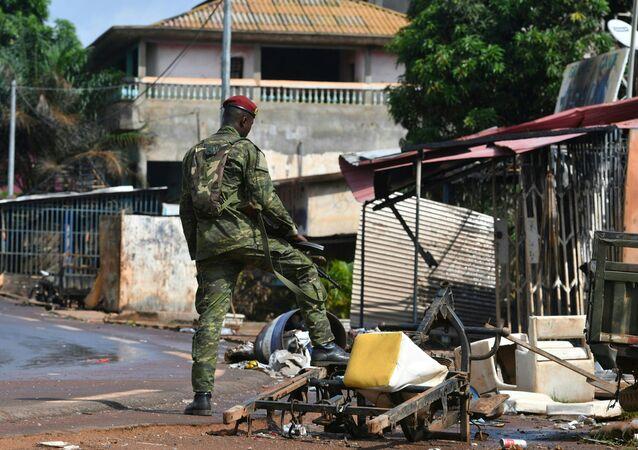 Un soldat ivoirien sur les décombres d'un magasin brûlé à M'Batto