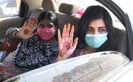 Des femmes tendent leur main décorées au henné
