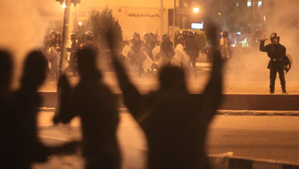 Egyptian protesters gesture as they clash with riot police at Cairo's landmark Tahrir Square on November 19, 2011, as Egyptian police fired rubber bullets and tear gas to break up a sit-in among whose organisers were people injured during the Arab Spring which overthrew veteran president Hosni Mubarak - Sputnik France