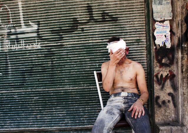 Dans ce dossier, photo prise le 4 septembre 2012, un Syrien blessé par un bombardement est assis sur une chaise devant un magasin fermé dans la zone d'Al-Muasalat à Alep. Lorsque les révoltes arabes qui balayaient la région et renversaient les autocrates comme des dominos ont atteint la Syrie, les jours de Bachar al-Assad à la tête de l'Etat semblaient comptés. Dix ans plus tard, il a cependant défié les obstacles, survivant à l'isolement international et à la perte temporaire des deux tiers du territoire national pour retrouver sa pertinence et s'accrocher au pouvoir. En mars 2011, lorsque des protestations ont éclaté en Syrie, il semblait douteux que la minorité alaouite au pouvoir soit capable de résister à la vague de soulèvements qui remodelait radicalement la région.