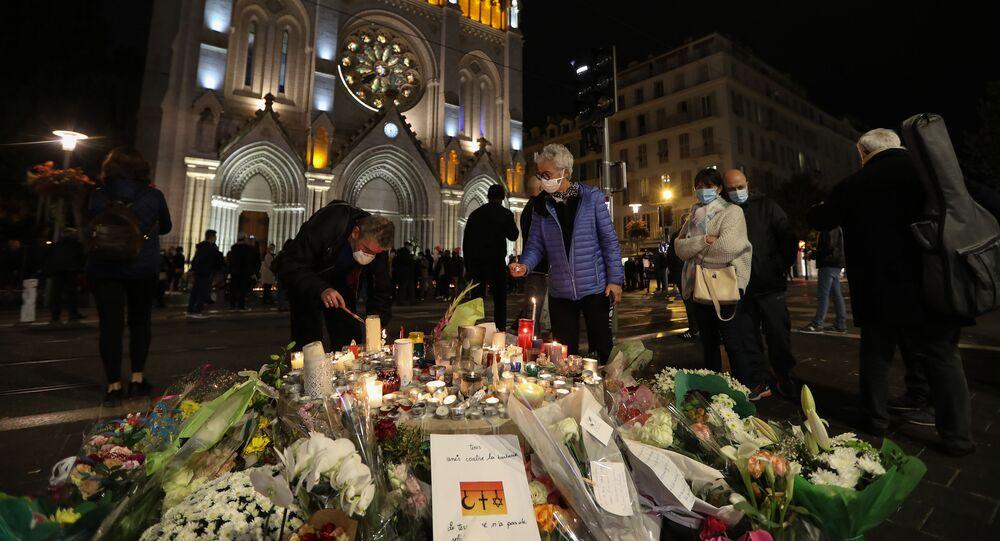 Des personnes allument des bougies en hommage aux victimes de l'attaque à la basilique Notre-Dame-de-l'Assomption de Nice