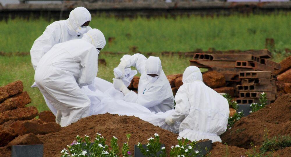 Des ambulanciers paramédicaux enterrent le corps d'une victime tuée par le virus Nipah en Inde, le 25 mai 2018