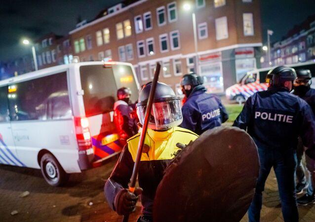 Un policier avec un casque et un bouclier tient un bâton alors qu'il se tient à côté d'un policier sur la Beijerlandselaan à Rotterdam, le 25 janvier 2021. - Les Pays-Bas ont été frappés par une deuxième vague d'émeutes le 25 janvier au soir, après que les manifestants se soient à nouveau déchaînés dans plusieurs villes suite à l'instauration d'un couvre-feu pour les coronavirus au cours du week-end. La police anti-émeute a affronté des groupes de manifestants dans la ville portuaire de Rotterdam, où ils ont utilisé un canon à eau. (Photo de Marco de Swart / ANP / AFP) / Netherlands OUT