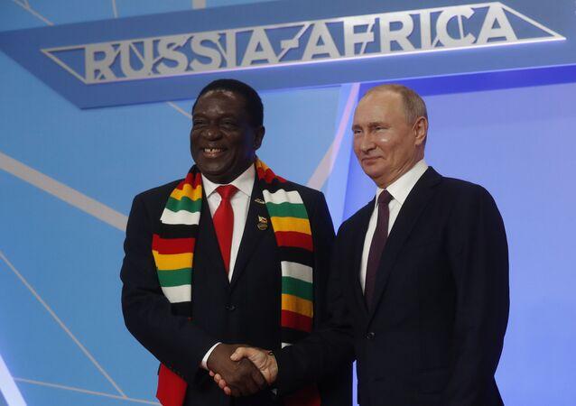 Le président russe Vladimir Poutine salue le président zimbabwéen Emmerson Mnangagwa lors de la cérémonie d'accueil officielle
