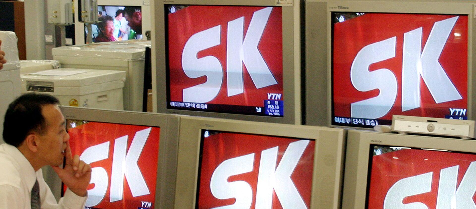 Un homme regarde les informations télévisées montrant le logo de SK Group, à Seoul, AFP PHOTO/KIM JAE-HWAN (Photo by KIM JAE-HWAN / AFP) - Sputnik France, 1920, 02.02.2021
