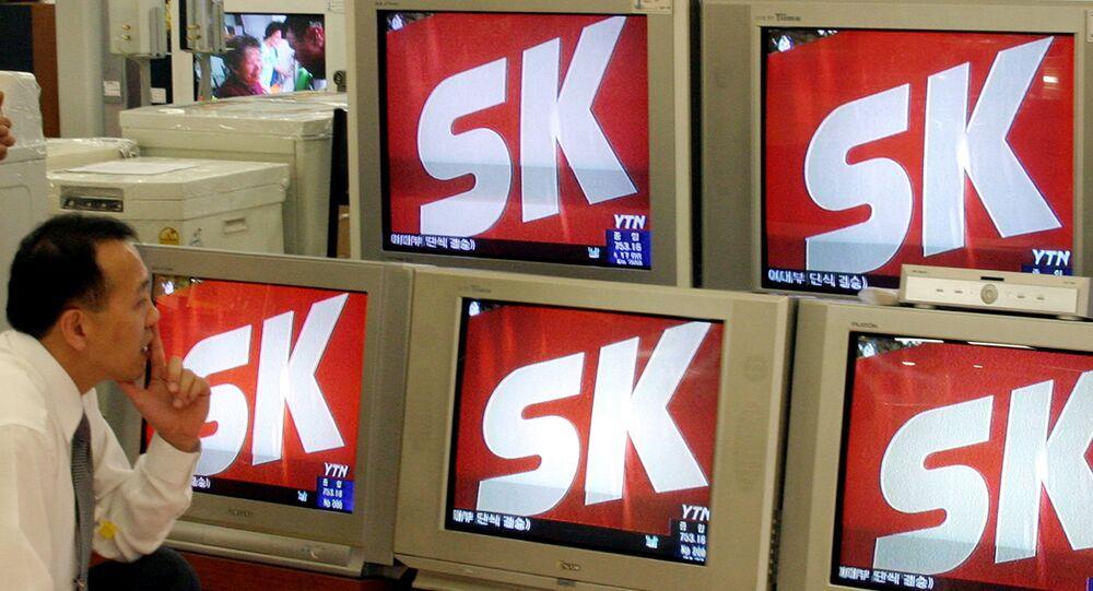 Un homme regarde les informations télévisées montrant le logo de SK Group, à Seoul, AFP PHOTO/KIM JAE-HWAN (Photo by KIM JAE-HWAN / AFP)