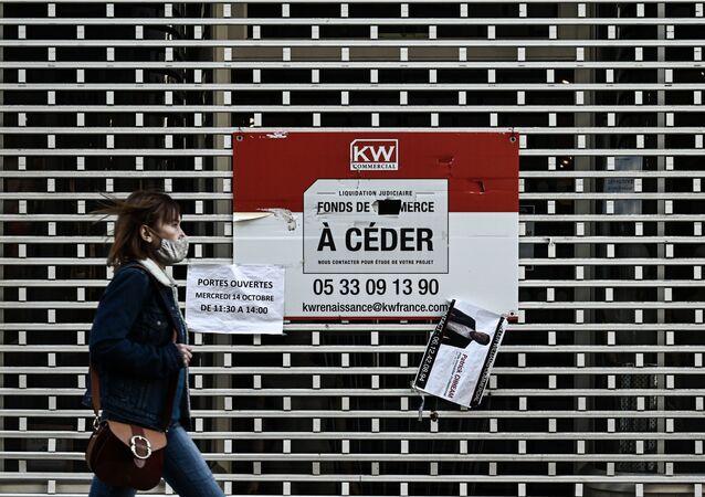 Personne portant un masque devant un magasin fermé à Bordeaux, novembre 2020