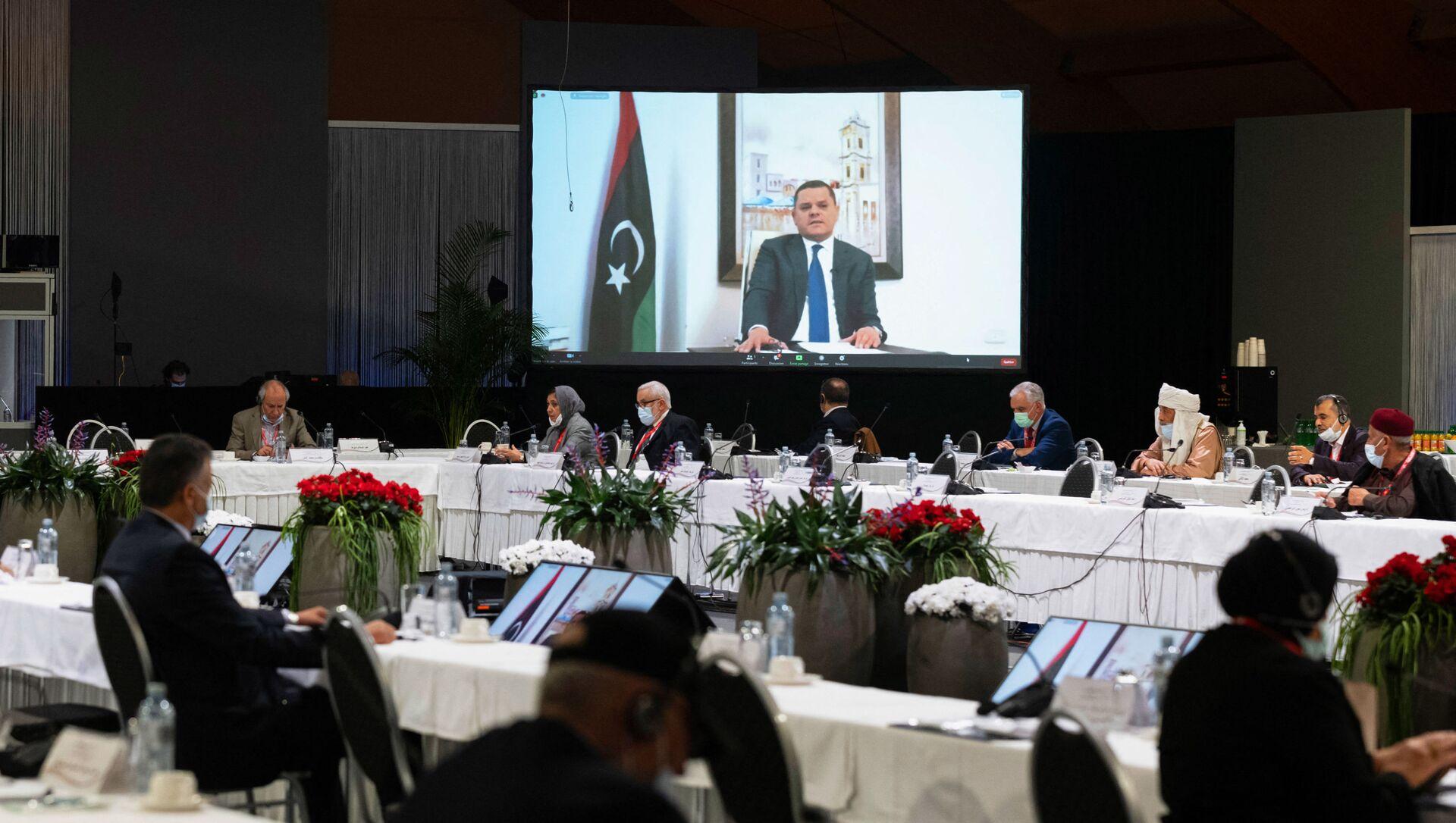 Cette photo prise le 3 février 2021 dans un lieu non divulgué près de Genève et diffusée par les Nations unies (ONU) montre Abdul Hamid Mohammed Dbeibah prononçant un discours par liaison vidéo lors d'une réunion du Forum de dialogue politique libyen (LPDF). - Les délégués libyens aux pourparlers facilités par les Nations unies le 5 février 2021 ont choisi Abdul Hamid Mohammed Dbeibah comme premier ministre de transition, ainsi qu'un conseil présidentiel de trois membres, pour gouverner ce pays d'Afrique du Nord ravagé par la guerre jusqu'aux élections de décembre. (Photo by Handout / UNITED NATIONS / AFP) / RESTRICTED TO EDITORIAL USE - MANDATORY CREDIT AFP PHOTO/ UNITED NATIONS - NO MARKETING - NO ADVERTISING CAMPAGNES - DISTRIBUTED AS A SERVICE TO CLIENTS - Sputnik France, 1920, 08.02.2021
