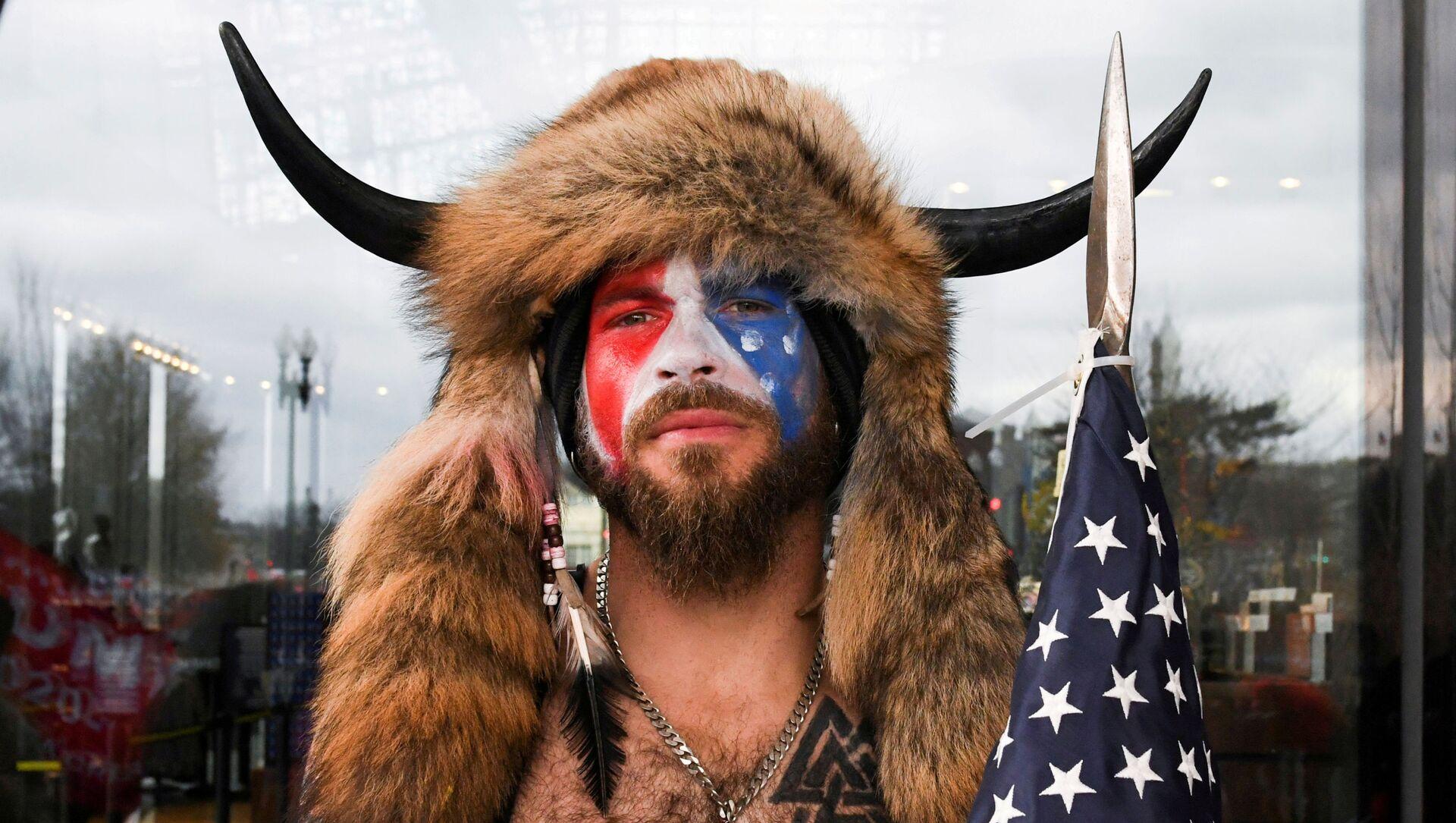 Jacob Anthony Chansley, également connu sous le nom de Jake Angeli, de l'Arizona, pose avec son visage peinturluré aux couleurs du drapeau des États-Unis tandis que les partisans de Donald Trump se réunissent à Washington le 6 janvier 2021 - Sputnik France, 1920, 12.02.2021