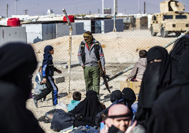 Un membre de la sécurité intérieure kurde monte la garde alors que des femmes conduisent des enfants avant leur départ, lors de la libération d'un autre groupe de familles syriennes du camp kurde d'al-Hol, qui détient des parents présumés de combattants du groupe de l'État islamique (IS), dans le gouvernorat de Hasakeh, au nord-est de la Syrie, le 28 janvier 2021. Delil SOULEIMAN / AFP