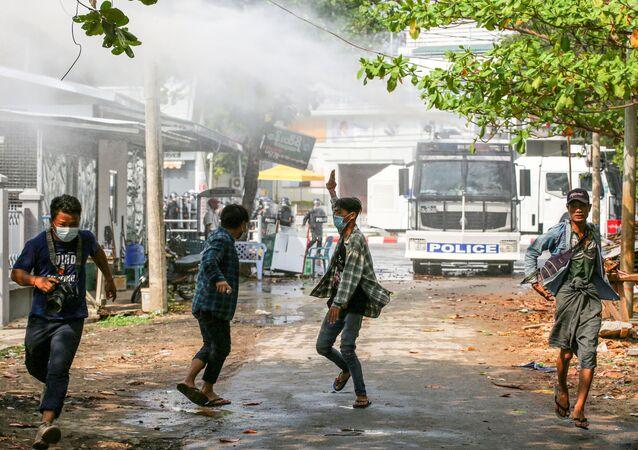 Des manifestants près d'un canon à eau dans la capitale de la Birmanie, Naypyidaw, le 18 février
