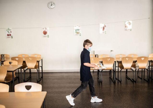 Un élève de collège tient son plateau dans la cantine de l'école Françoise-Giroud à Vincennes, septembre 2020