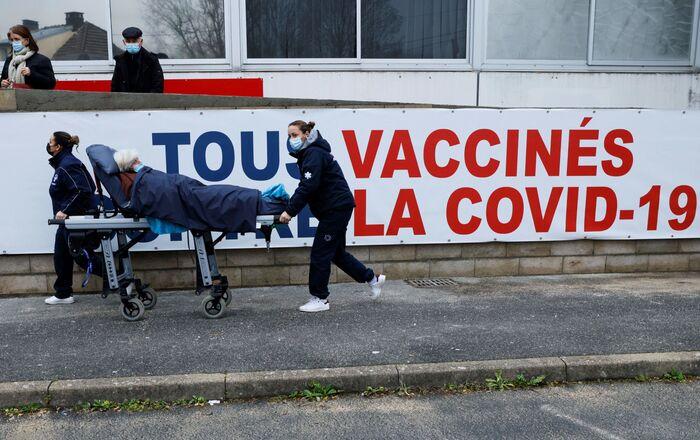 Une femme est transportée sur un brancard au centre de vaccination Covid-19 du Groupe Hospitalier Sud Ile-de-France à Melun, le 8 février 2021. (Photo by Thomas SAMSON / POOL / AFP)