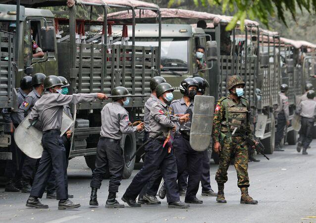 Des policiers et des militaires lors d'une manifestation contre le coup d'État à Mandalay, en Birmanie, le 20 février 2021