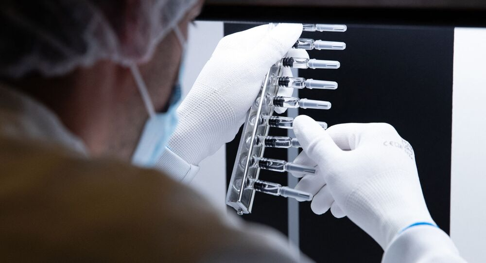 A laboratory technician inspects defunct syringes which were set aside by an automatic inspection machine at a French pharmaceutical company Sanofi's world distribution centre in Val de Reuil on July 10, 2020