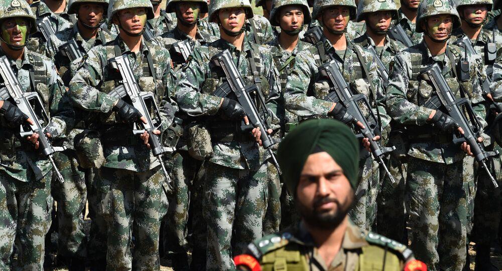Un soldat indien face à un groupe de militaires de l'Armée populaire de Libération en 2016. (Photo by INDRANIL MUKHERJEE / AFP)