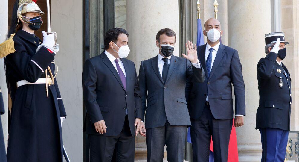 Le président français Emmanuel Macron (G) pose avec les dirigeants intérimaires de la Libye Mohamed El-Menfi (C) et Musa al-Koni (D) avant des entretiens au palais présidentiel de l'Elysée à Paris, le 23 mars 2021.