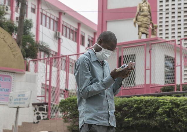 Un homme portant un masque devant l'entrée de l'hôpital de Yaoundé